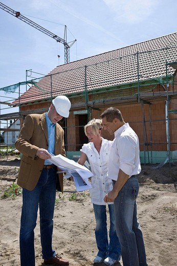 Architect and married couple looking at a construction plan in front of framing : Stock Photo