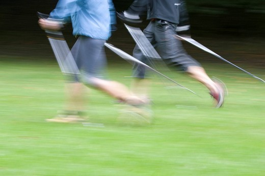 Two nordic walker with stick on a green meadow in the English Garden in Munich as a motion study : Stock Photo