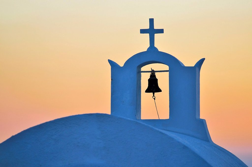 Bell and cross of a church in the last evening light with an orange-red sky, Oia, Ia, Santorin, Cyclades, Greece, Europe : Stock Photo