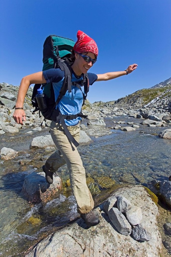 Stock Photo: 1848R-396722 Young woman jumping across a creek, hiking, backpacking, hiker with backpack, historic Chilkoot Trail, Chilkoot Pass, near Crater Lake, alpine tundra, Yukon Territory, British Columbia, B. C., Canada