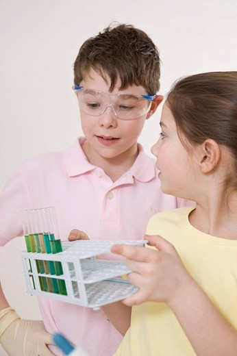 Stock Photo: 1848R-397636 Boy wearing safety glasses talking about the experiment with a girl, holding test tubes