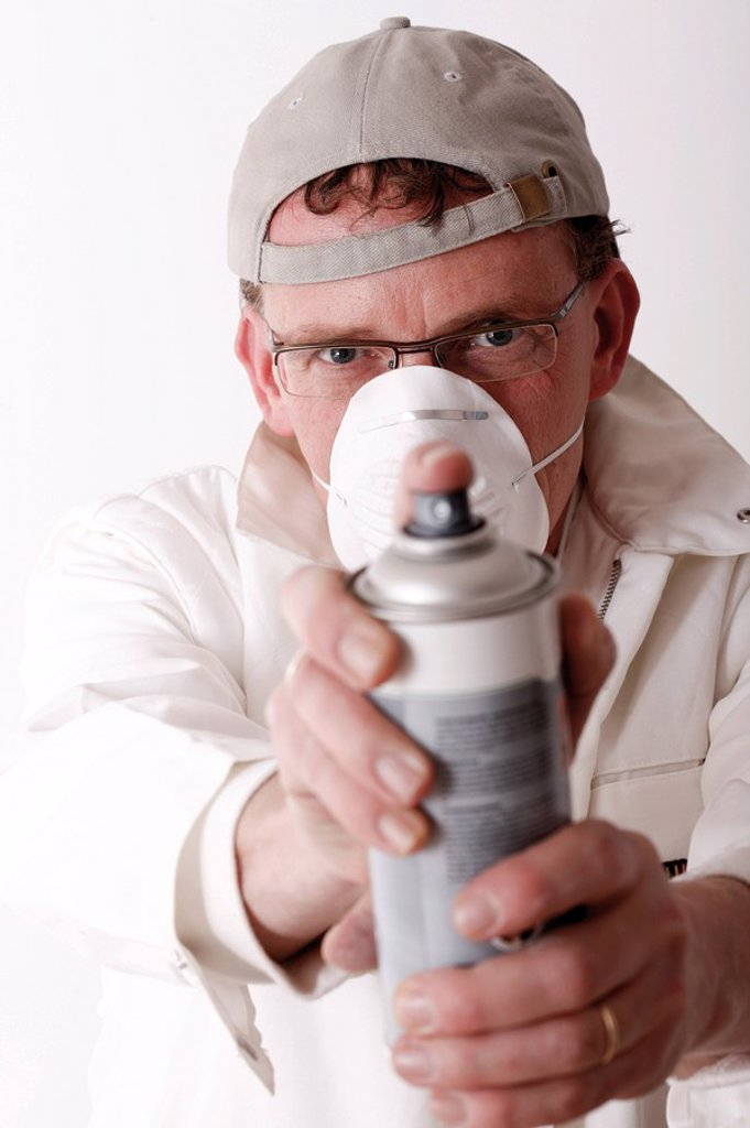 Workman, with breathing protection, holding a can of spray paint : Stock Photo