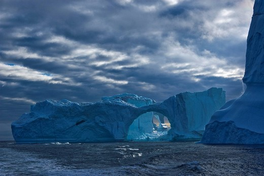 Iceberg in the shape of a gate, dramatic clouds, Disko Bay, Greenland, North Atlantic : Stock Photo