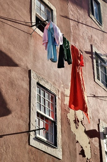 Stock Photo: 1848R-399723 Laundry hanging to dry on a line in front of a house with crumbling plaster walls in the district of Alfama, Lisbon, Portugal, Europe