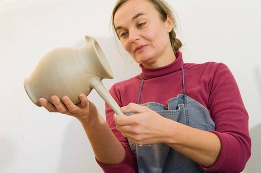 Stock Photo: 1848R-502887 Ceramic artist working in her workshop, pulling a handle for a pitcher, Geisenhausen, Bavaria, Germany, Europe