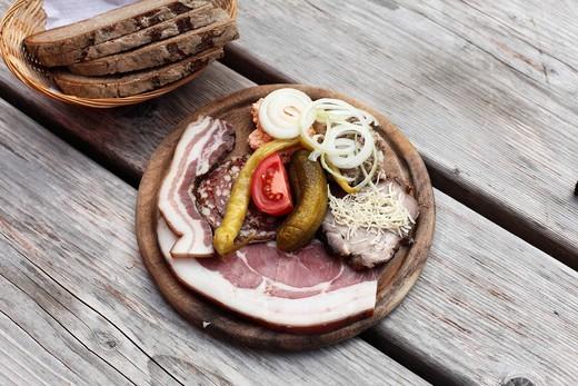 Peasant snack, hearty on wooden board, Brettljause, Koschutahaus mountain lodge, Karawanken, Carinthia, Austria, Europe : Stock Photo