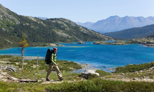 Young woman hiking, backpacking, hiker with backpack, historic Chilkoot Pass, Chilkoot Trail, Deep Lake behind, Yukon Territory, British Columbia, B. C., Canada : Stock Photo