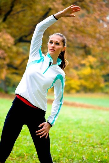 Young woman warming up as preparation for jogging : Stock Photo