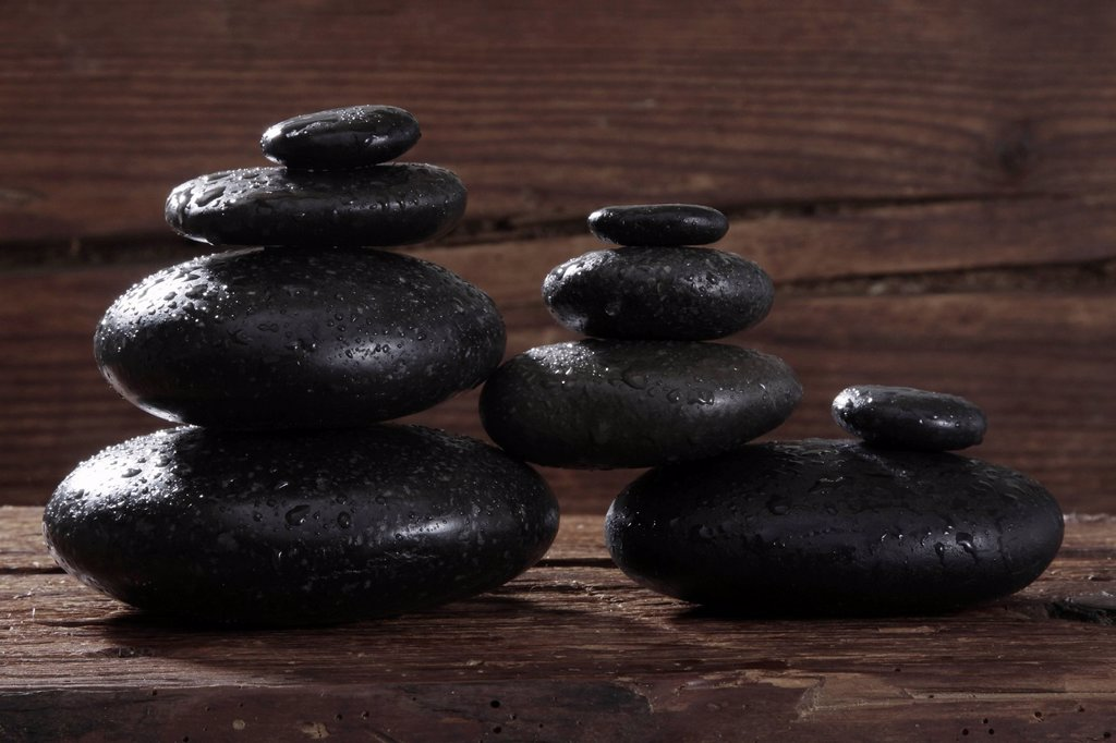 Hot stone massage stones on a wooden beam : Stock Photo