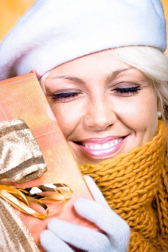 Stock Photo: 1848R-507228 Young woman with a wool scarf and a wrapped gift, portrait