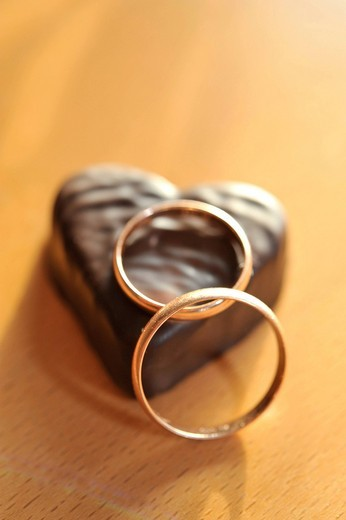 Stock Photo: 1848R-508033 Wedding rings on a chocolate heart