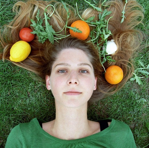 Young woman with vegetables and fruit in her hair : Stock Photo