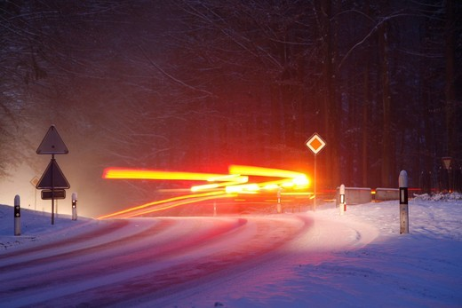 Slip hazard, hard_packed snow and ice, bend on snow_covered road, car trails in winter : Stock Photo