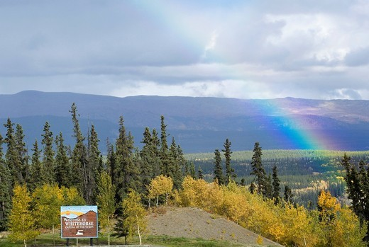 Stock Photo: 1848R-508655 Rainbow, Indian Summer, trees in fall colours, Whitehorse welcoming sign, Two Mile Hill, Whitehorse, capital of Yukon Territory, Canada
