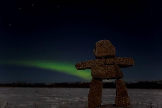 Inuit stone man, inukshuk, stone landmark or cairn, green Northern Lights, Polar Lights Aurora borealis, near Whitehorse, Yukon Territory, Canada : Stock Photo