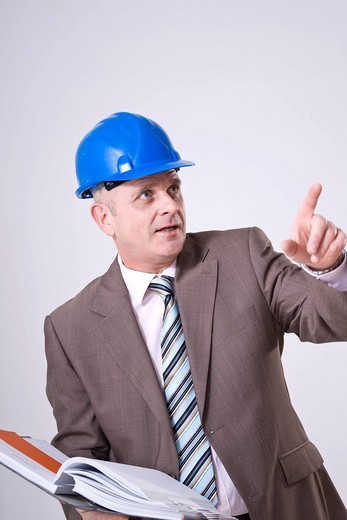 Man with hard hat and file pointing to one direction : Stock Photo