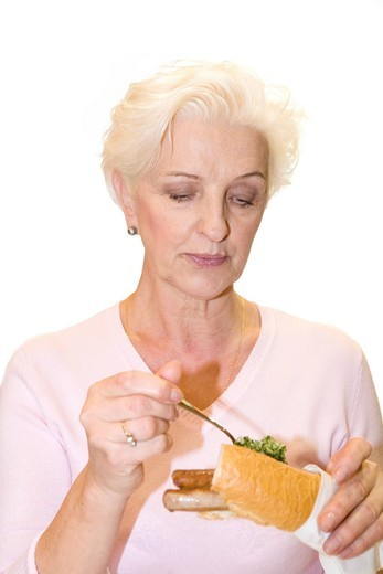 A woman putting parsley on a sausage in a baguette : Stock Photo