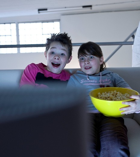 Children with popcorn watching television : Stock Photo