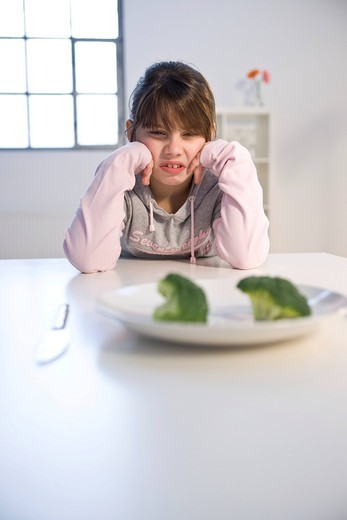 Girl sitting in front of a plate with broccoli in disgust : Stock Photo