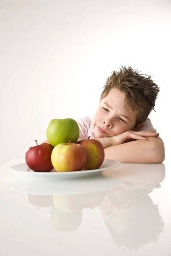 Boy sitting in front of a plate of apples, looking skeptical : Stock Photo