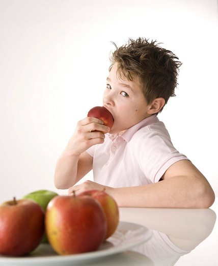 Stock Photo: 1848R-510102 A boy biting into a red apple
