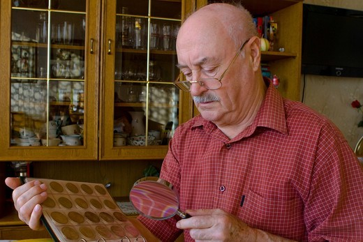 Stock Photo: 1848R-511104 Pensioner looking at his coin collection with a magnifying glass