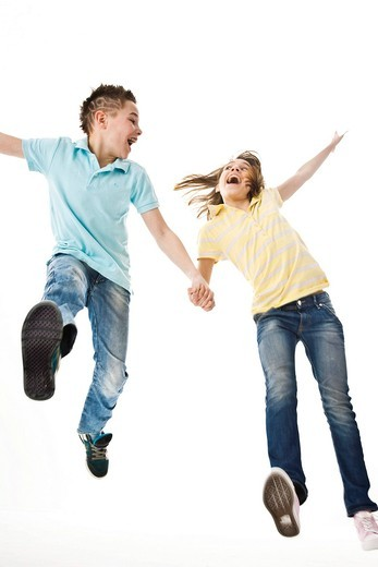 A boy and a girl leaping into the air together : Stock Photo