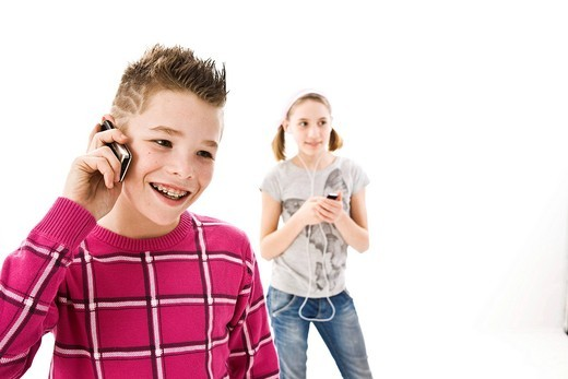 Boy with a mobile phone and a girl with an iPod : Stock Photo