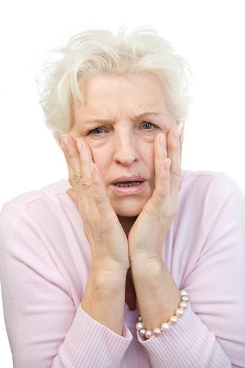 Stock Photo: 1848R-511770 Woman holding her hands in horror at her face