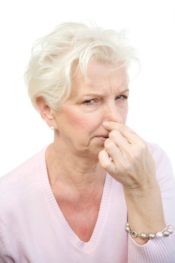Woman, 60, holding her nose in disgust : Stock Photo
