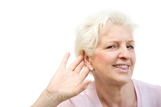 Old woman can´t hear something, puts hand behind her ear : Stock Photo