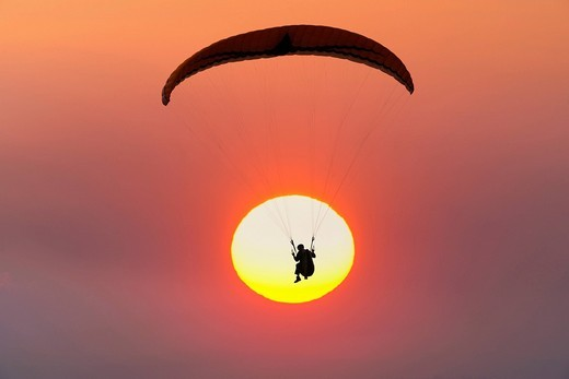Stock Photo: 1848R-512954 Paraglider in front of sun, sunset