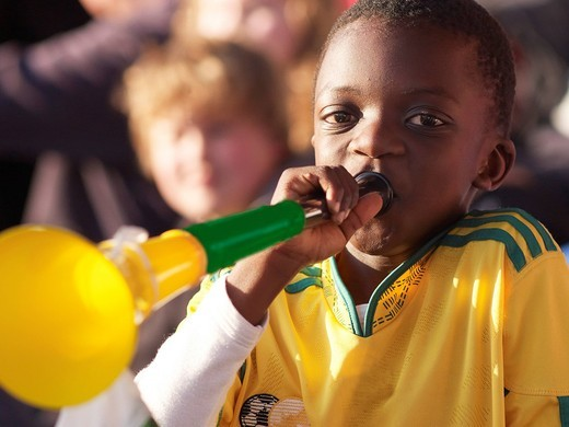 Stock Photo: 1848R-514395 South African boy wearing the South African national soccer team´s jersey trumpeting in a Vuvuzela