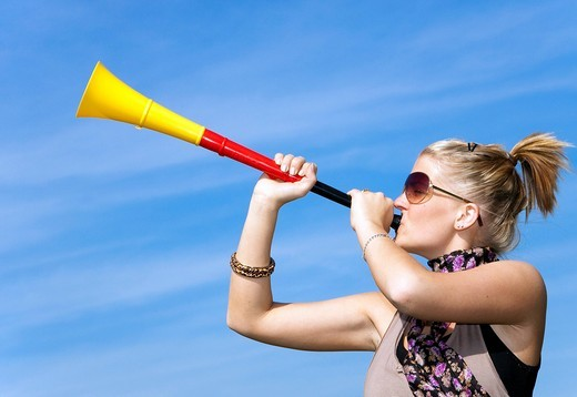 19_year_old woman blowing trumpet, fanfare horn in the colours of the German flag : Stock Photo