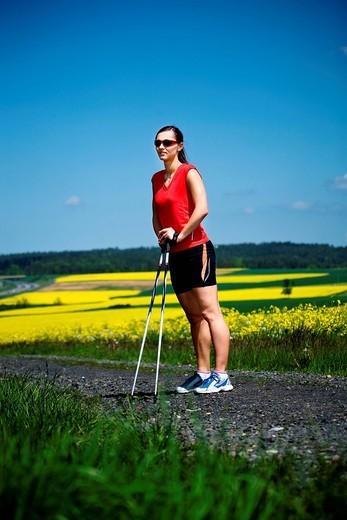 Young woman taking a break during Nordic walking : Stock Photo