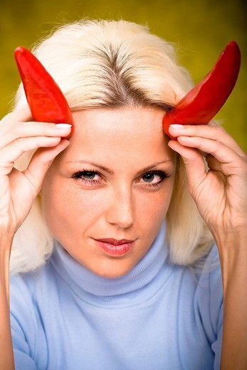 Portrait of a young woman with chilli peppers as horns : Stock Photo