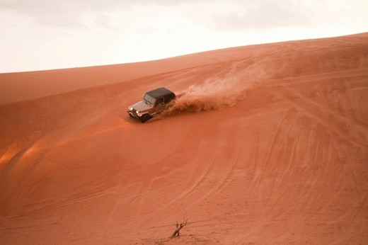 Stock Photo: 1848R-515651 Jeep driving down dune sidewards, Wahiba Sands, Oman, Middle East