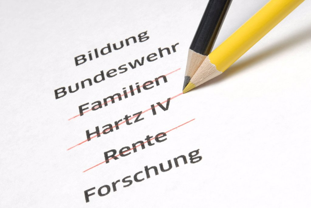 A yellow and a black pencil crossing out the letterings Familien, Hartz IV and Rente, German for families, Hartz IV, a German unemployment benefit, and pension, symbolic image for the policy of economy measures of the Conservative Parties in Germany : Stock Photo