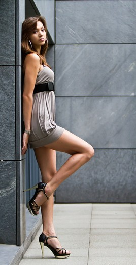 Young woman in a short gray dress and high heels posing, leaning against wall : Stock Photo
