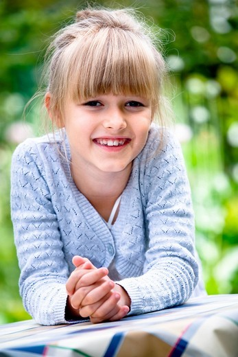 Girl at a table in the garden : Stock Photo
