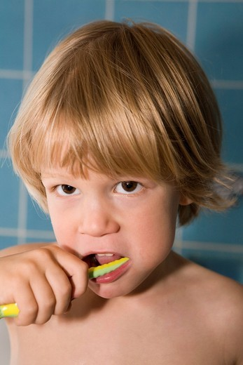 Four_year_old blond boy brushing his teeth : Stock Photo