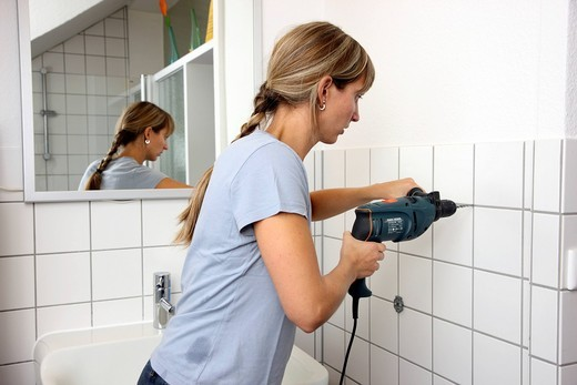 Stock Photo: 1848R-519356 Young woman drilling a hole in a tiled bathroom wall