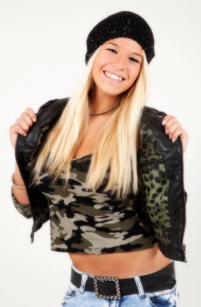 Young woman with long blond hair posing while wearing a jacket, a military_top : Stock Photo