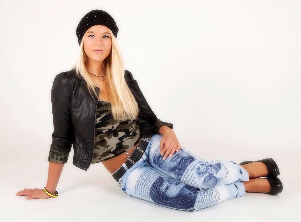 Stock Photo: 1848R-522458 Young woman with long blond hair posing while seated and wearing a jacket, a military_top and light blue jeans