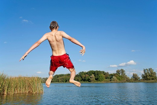 Stock Photo: 1848R-522578 Boy jumping off a bridge into a lake, Teterow, Mecklenburg_Western Pomerania, Germany, Europe