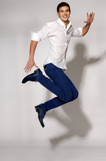 Young man in white shirt and blue jeans jumping : Stock Photo