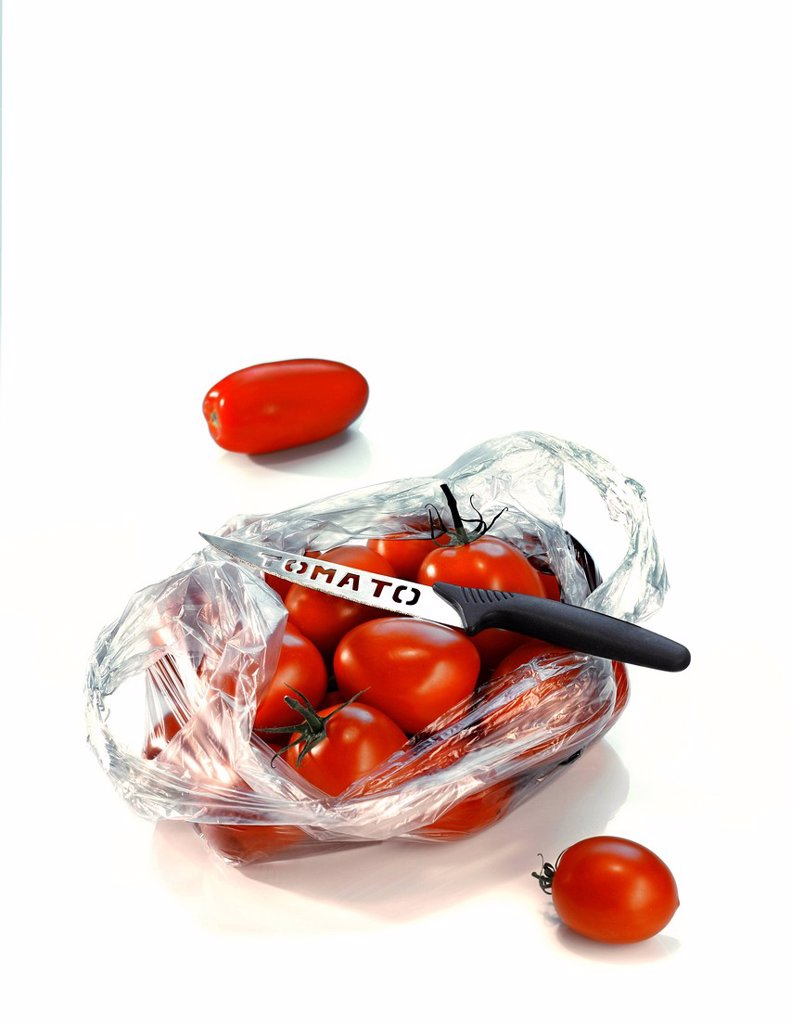 Tomatoes in a plastic bag with a tomato knife : Stock Photo
