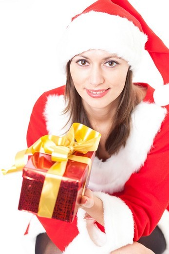 Woman in Christmas costume giving a gift : Stock Photo