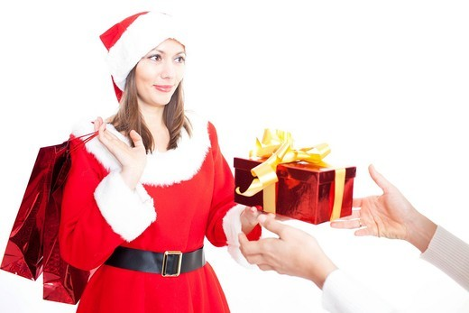 Woman in Santa Claus costume giving a gift : Stock Photo