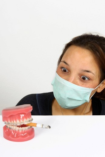 Stock Photo: 1848R-523628 Symbolic image for adolescent smokers, young woman looking in horror at dentures with fixed braces and a smoking cigarette